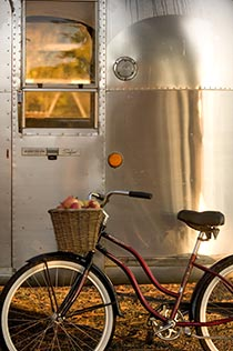 Silver airstream trailer with old-fashioned cruiser bike leaning against it