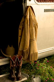 Fringed leather jacket and cowgirl boots set on doorstep of silver airstream